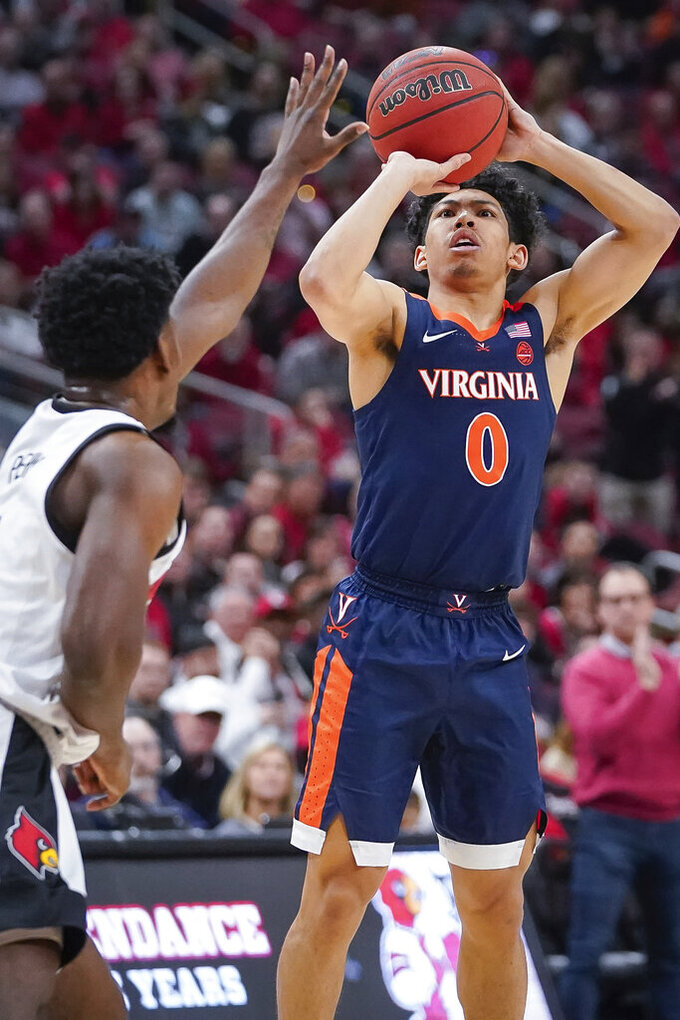 Virginia guard Kihei Clark (0) shoots the ball during an NCAA college basketball game against Louisville, Saturday, Feb 8, 2020 in Louisville, Ky. (AP Photo/Bryan Woolston)