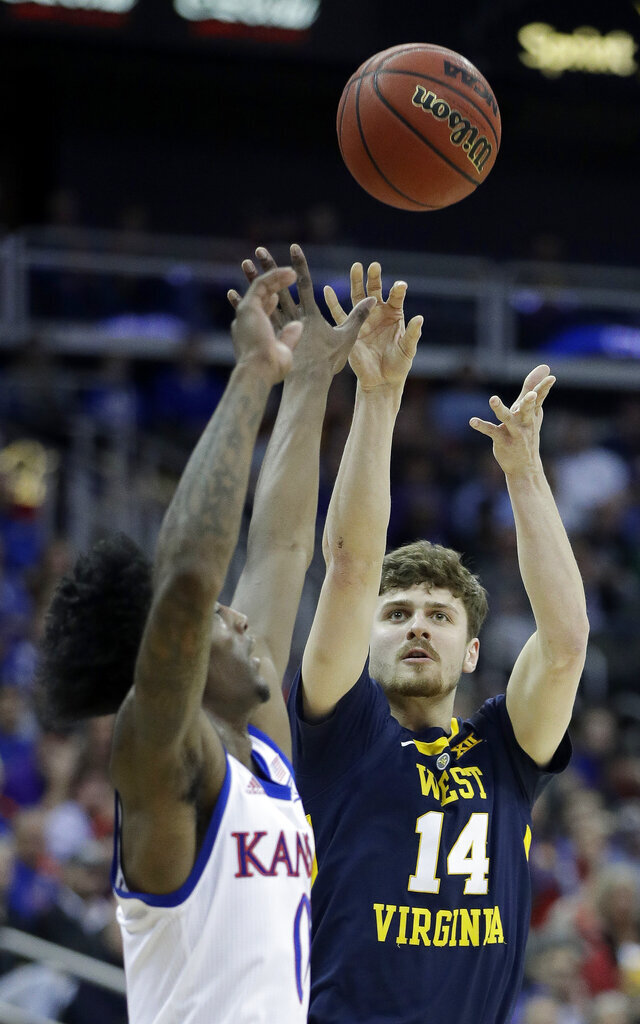 West Virginia's Chase Harler (14) shoots under pressure from Kansas' Marcus Garrett during the first half of an NCAA college basketball game in the Big 12 men's tournament Friday, March 15, 2019, in Kansas City, Mo. (AP Photo/Charlie Riedel)