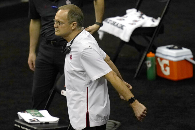 Oklahoma head coach Lon Kruger stretches during a timeout in the first half of an NCAA college basketball game against Kansas in the quarterfinal round of the Big 12 men's tournament in Kansas City, Mo., Thursday, March 11, 2021. (AP Photo/Orlin Wagner)