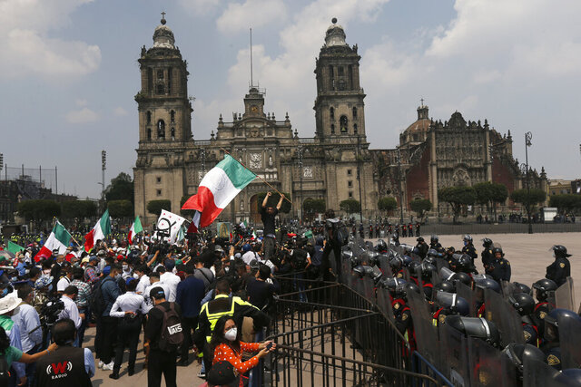 Police in riot gear block demonstrators who are demanding the resignation of Mexican President Andrés Manuel López Obrador, commonly known by his initials AMLO, from entering Mexico City's main square the Zocalo, Wednesday, Sept. 23, 2020. (AP Photo/Marco Ugarte)