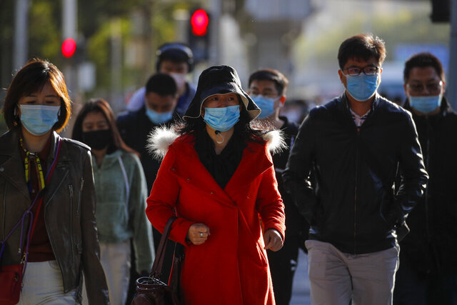 Pedestrians wearing face masks to help curb the spread of the coronavirus walk on a street during the morning rush hour in Beijing, Wednesday, Oct. 21, 2020. (AP Photo/Andy Wong)