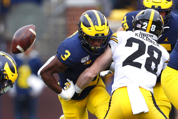 Michigan running back Christian Turner (3) fumbles as Iowa defensive back Jack Koerner (28) makes a tackle during the first half of an NCAA college football game in Ann Arbor, Mich., Saturday, Oct. 5, 2019. (AP Photo/Paul Sancya)