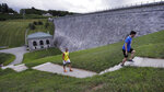 In this July 25, 2018, photograph, men climb stairs while working out at the Wachusett Reservoir Dam in Clinton, Mass.  The dam, which holds up to 65 billion gallons of water, is considered high hazard because of its destructive potential should it fail but also is rated as in satisfactory condition. It is inspected monthly according to the Massachusetts Department of Conservation and Recreation. (AP Photo/Charles Krupa)