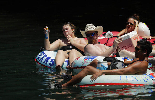 Tubers float the Comal River in New Braunfels, Texas, Wednesday, May 20, 2020. As parks reopen following closures due to the COVID-19 pandemic, many Texans are returning to the outdoors. (AP Photo/Eric Gay)