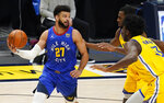 Denver Nuggets guard Jamal Murray, left, looks to pass the ball as Golden State Warriors center James Wiseman, front right, and forward Andrew Wiggins defend in the first half of an NBA basketball game late Thursday, Jan. 14, 2021, in Denver. (AP Photo/David Zalubowski)