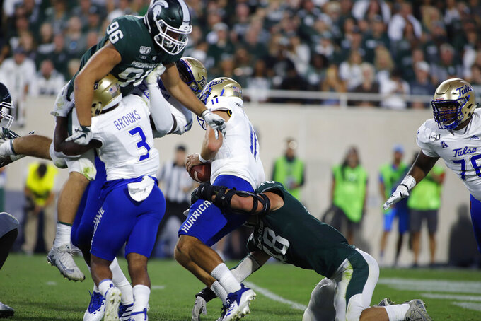 Michigan State's Kenny Willekes, bottom right, sacks Tulsa quarterback Zach Smith (11), causing a fumble, as Tulsa's Shamari Brooks (3) and Denzel Carter, left rear, block Michigan State's Jacub Panasiuk (96) during the second quarter of an NCAA college football game, Friday, Aug. 30, 2019, in East Lansing, Mich. (AP Photo/Al Goldis)