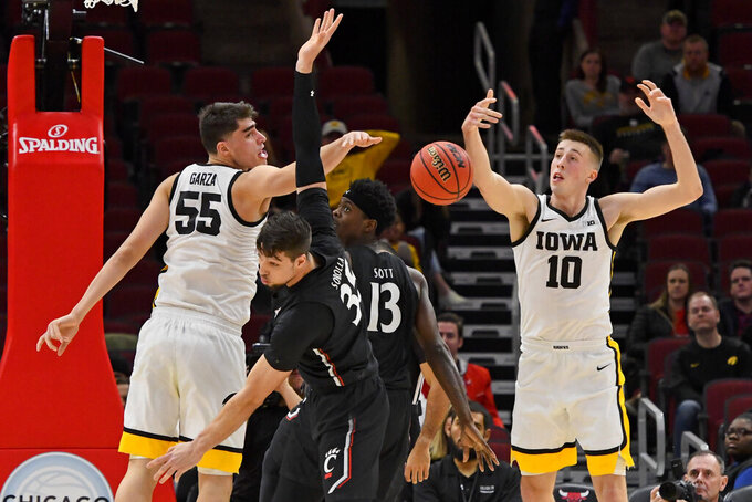 Cincinnati center Jaume Sorolla, front, and forward Tre Scott (13) chase the ball as do Iowa center Luka Garza (55) and guard Joe Wieskamp (10) during the first half of an NCAA college basketball game Saturday, Dec. 21, 2019, in Chicago. (AP Photo/Matt Marton)