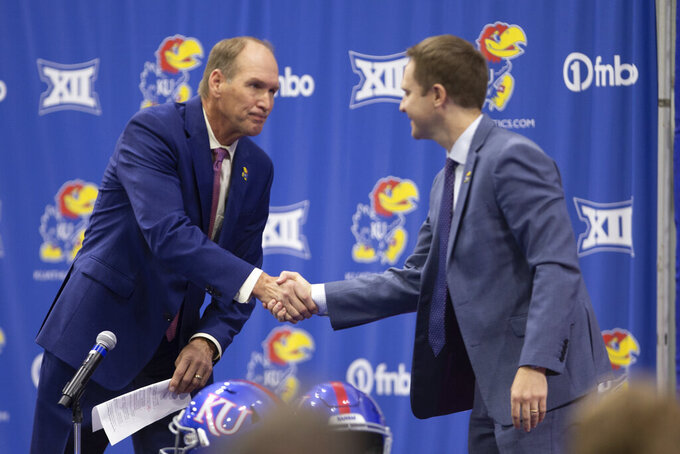 University of Kansas new football coach Lance Leipold, left, shakes hands with athletic director Travis Goff, during an introductory press conference in Lawrence, Kansas, Monday, May 3, 2021.  (Evert Nelson/The Topeka Capital-Journal via AP)