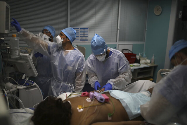 A medical crew works at a patient affected with COVID-19 in a Marseille hospital, southern France, Thursday, Sept.10, 2020. As the Marseille region has become France's latest virus hotspot, hospitals are re-activating emergency measures in place when the pandemic first hit to ensure they're able to handle growing new cases. (AP Photo/Daniel Cole)