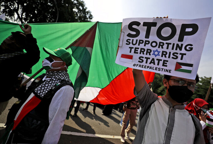 Protesters display a poster and Palestinian flags during a rally condemning Israeli attacks on the Palestinians, outside the U.S. Embassy in Jakarta, Indonesia, Tuesday, May 18, 2021. Pro-Palestinian protesters marched to the heavily guarded embassy on Tuesday to demand an end to Israeli airstrikes in the Gaza Strip. (AP Photo/Dita Alangkara)