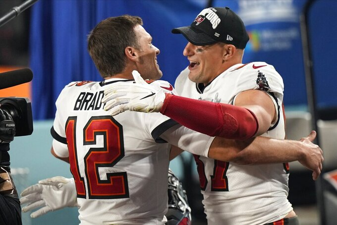 Tampa Bay Buccaneers quarterback Tom Brady and Tampa Bay Buccaneers tight end Rob Gronkowski embrace after the NFL Super Bowl 55 football game, Sunday, Feb. 7, 2021, in Tampa, Fla. The Buccaneers defeated the Chiefs 31-9 to win the Super Bowl. (AP Photo/David J. Phillip)