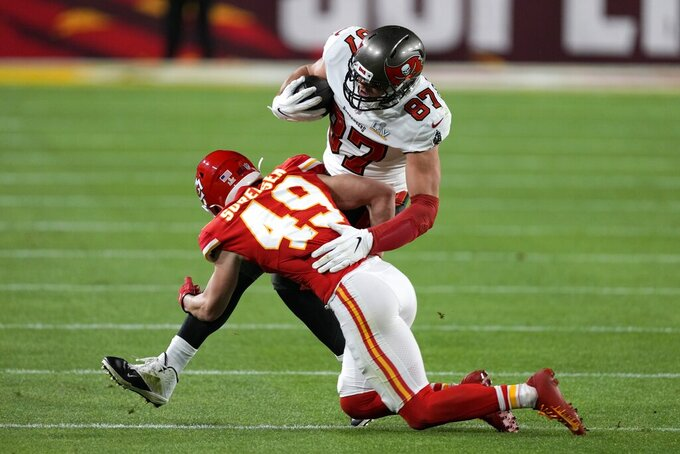 Tampa Bay Buccaneers tight end Rob Gronkowski (87) is tackled by Kansas City Chiefs free safety Daniel Sorensen (49) after catching a pass during the first half of the NFL Super Bowl 55 football game, Sunday, Feb. 7, 2021, in Tampa, Fla. (AP Photo/Chris O'Meara)