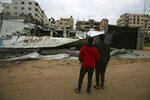 Palestinians check the damage of destroyed building belongs to Hamas ministry of prisoners hit by Israeli airstrikes in Gaza City, early Friday, Friday, March 15, 2019. Israeli warplanes attacked militant targets in the southern Gaza Strip early Friday in response to a rare rocket attack on the Israeli city of Tel Aviv, as the sides appeared to be hurtling toward a new round of violence. (AP Photo/Adel Hana)