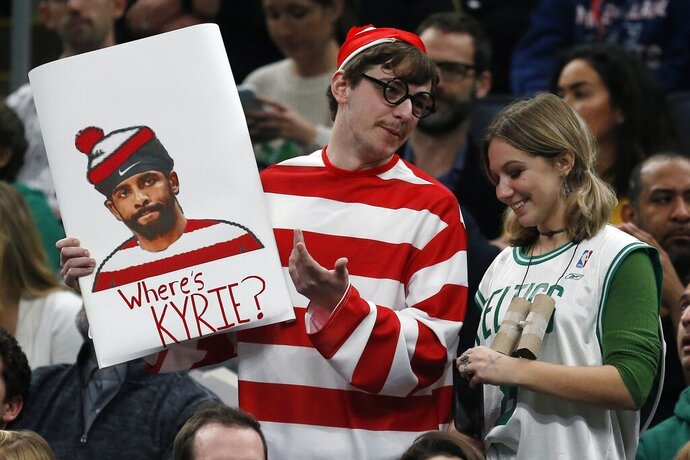 A Boston Celtics fan holds a sign asking about Brooklyn Nets' Kyrie Irving during the first half of an NBA basketball game in Boston, Wednesday, Nov. 27, 2019. (AP Photo/Michael Dwyer)