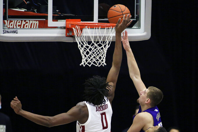 Washington guard Erik Stevenson, right, shoots while pressured by Washington State center Efe Abogidi during the second half of an NCAA college basketball game in Pullman, Wash., Monday, Feb. 15, 2021.  (AP Photo/Young Kwak)
