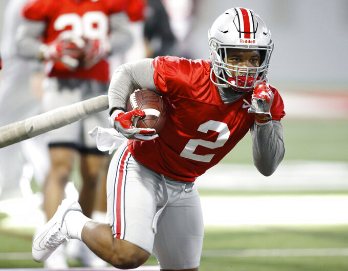 "FILE - In this Wednesday, March 6, 2019 file photo, Ohio State running back J.K. Dobbins runs through a drill during an NCAA college football practice in Columbus, Ohio. J.K. Dobbins wants to make up for his ""failure"" last season. Despite rushing for over 1,000 yards, Dobbins calls 2018 a disappointment. He had a drop-off from his record-breaking freshman year and is determined to get back to that level and prove he's best running back in the nation.(AP Photo/Paul Vernon, File)"