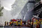 Fire engines attend to a fire in the central business district of Aukland New Zealand, Tuesday, Oct. 22, 2019. A large fire that broke out on the roof of a convention center that's under construction in downtown Auckland sent plumes of thick black smoke over New Zealand's largest city. (Michael Craig/New Zealand Herald photograph via AP)