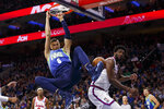 Dallas Mavericks' Kristaps Porzingis (6) dunks against Philadelphia 76ers'Joel Embiid, right, during the first half of an NBA basketball game, Friday, Dec. 20, 2019, in Philadelphia. (AP Photo/Chris Szagola)