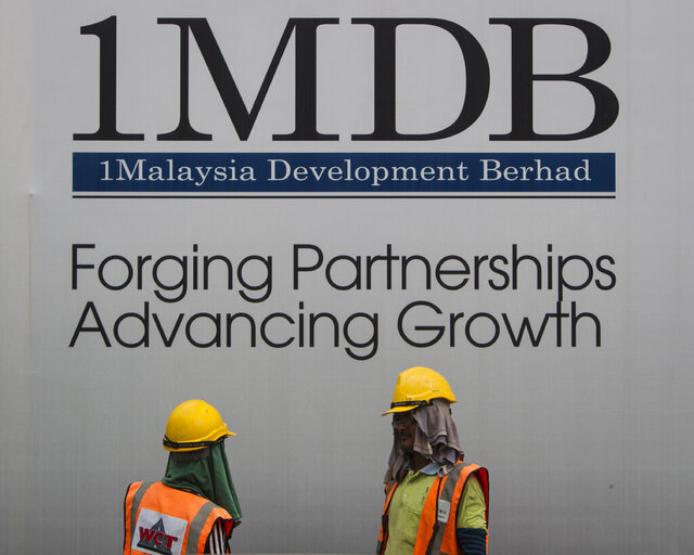 FILE - In this May 14, 2015 file photo, construction workers chat in front of a billboard for state investment fund 1 Malaysia Development Berhad (1MDB) at the fund's flagship Tun Razak Exchange development in Kuala Lumpur, Malaysia. Goldman Sachs reaches $3.9 billion settlement with Malaysia over scandal-plagued 1MDB sovereign wealth fund. (AP Photo/Joshua Paul, File)