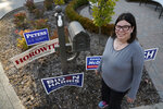 Lori Goldman poses for a portrait next to campaign signs outside her home in Bloomfield Village, Mich., Friday, Oct. 9, 2020. For most of her life, until 2016, Goldman had been politically apathetic. Had you offered her $1 million, she says, she could not have described the branches of government in any depth. She voted, sometimes. (AP Photo/Paul Sancya)