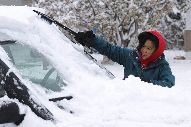 Meg Jones cleans the snow off her car outside her house on 2nd Avenue in Scottsbluff, Neb., Tuesday morning, Nov. 16, 2019.