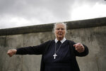 In this Sept. 18, 2019, photo, Sister Brigitte Queisser of the Lutheran Lazarus Order talks in front of concrete remains of the Berlin Wall during an interview with The Associated Press in Berlin. As Germany prepares to celebrate the 30th anniversary of the fall of the wall on Nov. 9, it also commemorates those who were arrested, injured or died as they sought to escape by tunneling under the wall, swimming past it, or climbing or flying over it. Many succeeded flawlessly. But Sister Brigitte witnessed first-hand the consequences for those who weren't able to pull it off quite so smoothly. (AP Photo/Markus Schreiber)