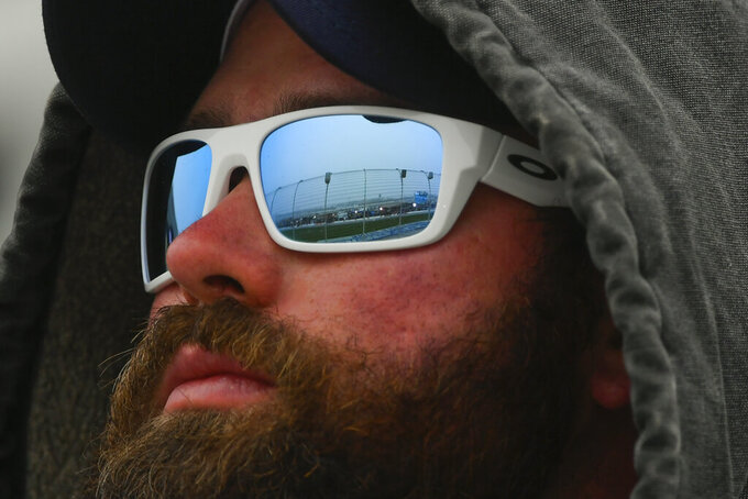 A track fence and lights on pit row are reflected in a fan's glasses as he watches the NASCAR Xfinity auto race at Atlanta Motor Speedway, Saturday, Feb. 23, 2019, in Hampton, Ga. (AP Photo/John Amis)