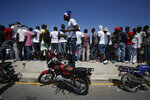 Protesters climb up on motorcycles and a highway barrier to try to get a look at thousands of demonstrators coming to join the march, in Petion-Ville, Port-au-Prince, Haiti, Sunday, Oct. 13, 2019. Thousands of Haitians joined a largely peaceful protest called by the art community Sunday to demand Moïse resign, increasing pressure on the embattled leader after nearly a month of marches that have shuttered schools and businesses.(AP Photo/Rebecca Blackwell)