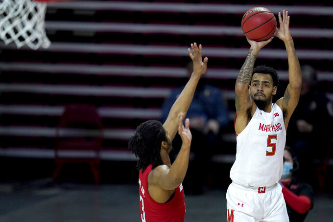 Maryland guard Eric Ayala (5) shoots against Nebraska forward Derrick Walker (13) during the second half of an NCAA college basketball game, Wednesday, Feb. 17, 2021, in College Park, Md. (AP Photo/Julio Cortez)