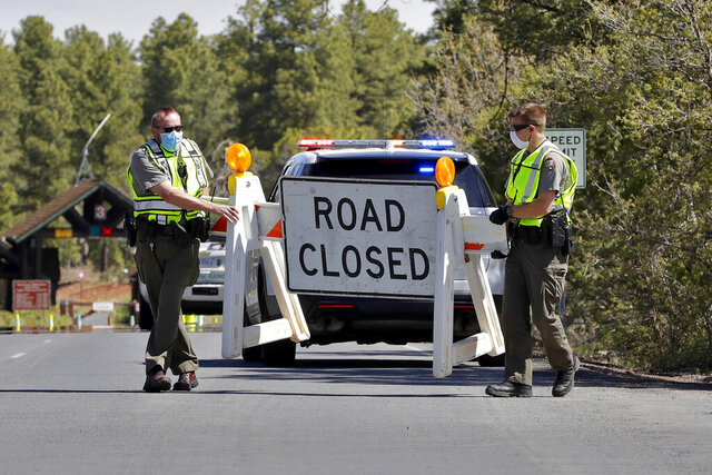 FILE - In this May 15, 2020, file photo U.S. Park Rangers close the entrance to the Grand Canyon in Grand Canyon, Ariz. The Grand Canyon is expanding access to its more popular South Rim entrance and planning to let visitors in around the clock next month after it shuttered temporarily over coronavirus concerns. The entrance station will be open from 4 a.m. until 2 p.m., starting Friday, May 30, 2020, until June 5, 2020, when the national park will drop restrictions on the hours the park said Thursday, May 28, 2020. (AP Photo/Matt York, File)