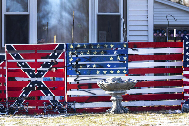 In this Wednesday, Dec. 11, 2019 photo, vandals have defaced the artwork and property of William Stark, an Iowa man who displayed paintings of Confederate flags and swastikas in his front yard. The Des Moines Register says the vandal or vandals scrawled the words