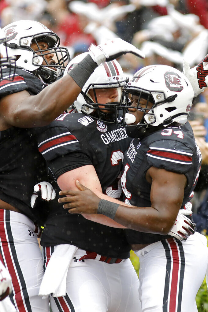 South Carolina's Mon Denson (34) is congratulated by teammates after scoring a touchdown against Florida in the first half of an NCAA college football game Saturday, Oct. 19, 2019, in Columbia, SC. (AP Photo/Mic Smith)