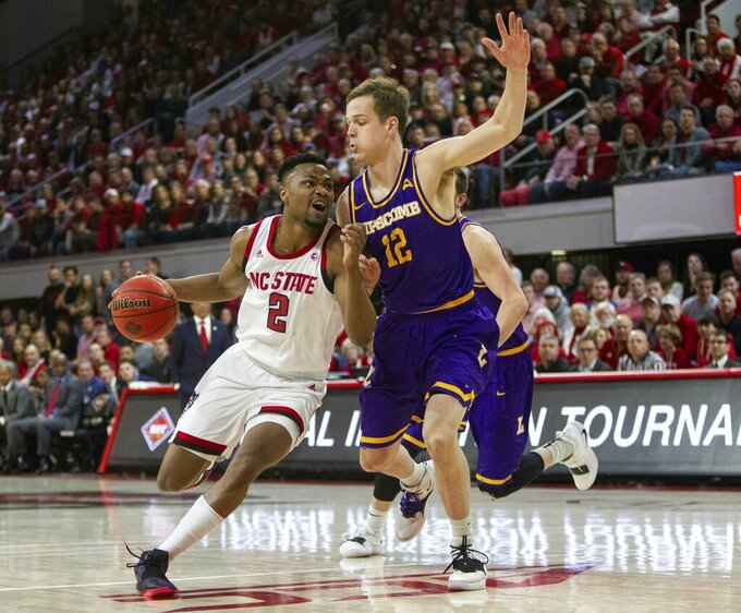 North Carolina State's Torin Dorn (2) dribbles past Lipscomb's Matt Rose (12) during the first half of an NCAA college basketball game in the quarterfinals of the NIT on Wednesday, March 27, 2019, in Raleigh, N.C. (Travis Long/The News & Observer via AP)