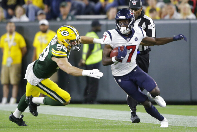 Houston Texans wide receiver Vyncint Smith breaks the tackle of Green Bay Packers linebacker Brady Sheldon during the second half of an NFL preseason football game Thursday, Aug. 8, 2019, in Green Bay, Wis. (AP Photo/Jeffrey Phelps)