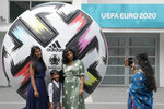 People take photographs beside a large football outside of Wembley stadium in London, Friday, July 9, 2021. The Euro 2020 soccer championship final match between Italy and England will be played at Wembley stadium on Sunday. (AP Photo/Frank Augstein)