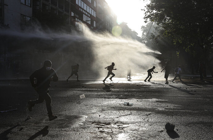 Anti-government protesters run amid the spray of a police water cannon during demonstrations against economic inequality in Santiago, Chile, Wednesday, Oct. 30, 2019. Chilean President Sebastian Pinera cancelled two major international summits after nearly two weeks of nationwide protests that have left at least 20 dead and damaged businesses and infrastructure around the country. (AP Photo/Esteban Felix)