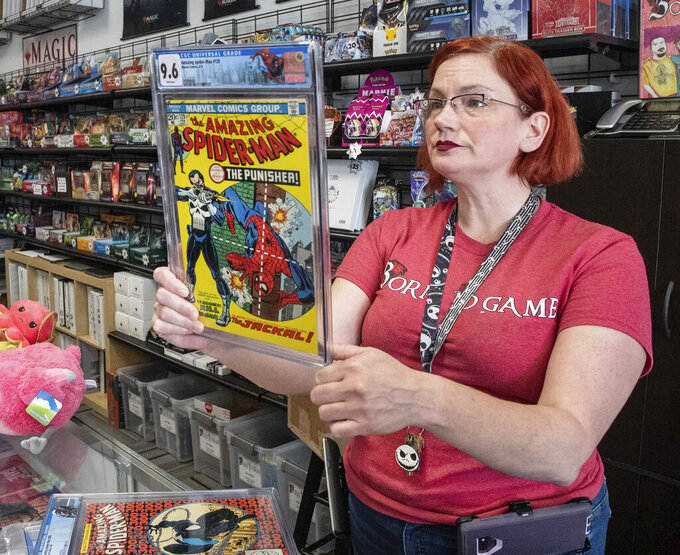 """HBorn To Game manager Crystal Burnett examines the graded AM129 Spiderman """"The Punisher"""" first issue with a worth of $13,000., Sept. 10, 2021, in South Dover, Del. Born to Game sells trading card games, board games, miniatures, comics, gaming and fantasy books, collectibles, and all things game related. (Marc Clery/Delaware State News via AP)"""