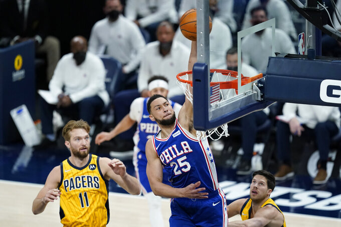 Philadelphia 76ers' Ben Simmons (25) dunks against Indiana Pacers' Domantas Sabonis (11) during the first half of an NBA basketball game, Tuesday, May 11, 2021, in Indianapolis. (AP Photo/Darron Cummings)