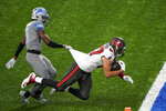 Tampa Bay Buccaneers tight end Rob Gronkowski (87) defended by Detroit Lions defensive back Tracy Walker (21) falls into the end zone for a touchdown during the first half of an NFL football game, Saturday, Dec. 26, 2020, in Detroit. (AP Photo/Carlos Osorio)