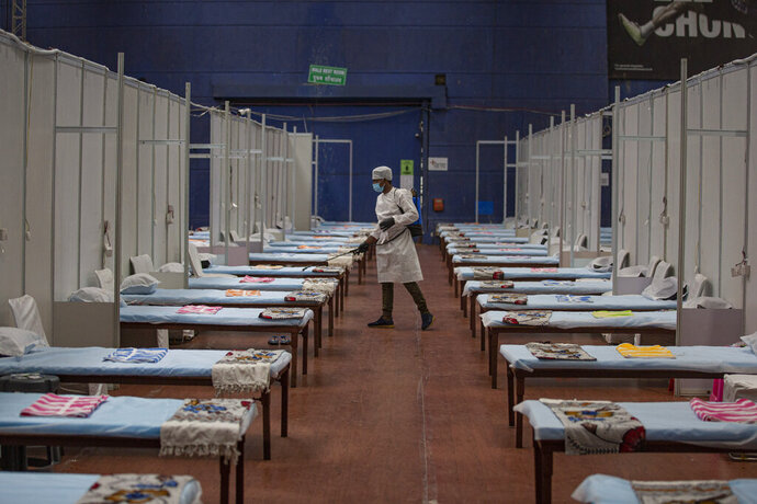 A man sanitizes a makeshift COVID-19 care center at an indoor sports stadium in New Delhi, India, Wednesday, July 8, 2020. India has overtaken Russia to become the third worst-affected nation by the coronavirus pandemic. (AP Photo/Altaf Qadri)