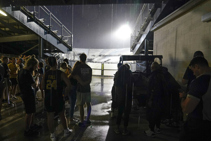 Fans seek shelter under the seating area of the stadium during a lightning weather delay before an NCAA college football game between Central Florida and Boise State, Thursday, Sept. 2, 2021, in Orlando, Fla. (AP Photo/John Raoux)