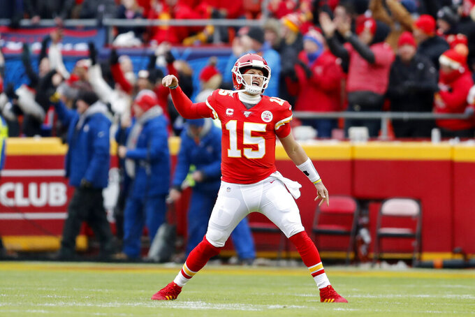 Kansas City Chiefs quarterback Patrick Mahomes (15) reacts after a touchdown by tight end Travis Kelce during the first half of an NFL divisional playoff football game against the Houston Texans, in Kansas City, Mo., Sunday, Jan. 12, 2020. (AP Photo/Jeff Roberson)