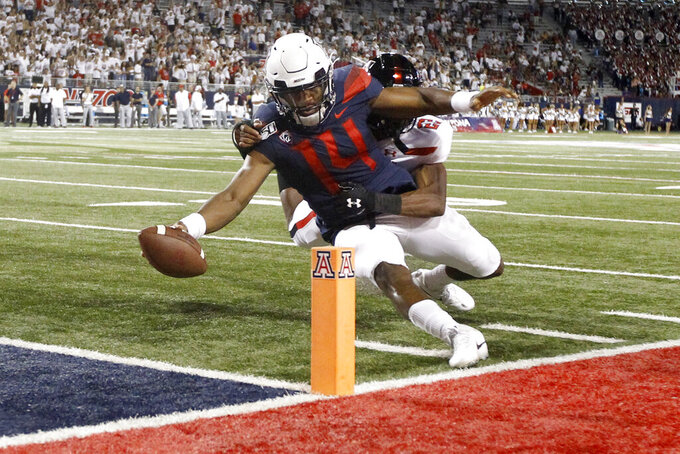 Arizona quarterback Khalil Tate (14) tries to extend the ball past the end zone pylon before stepping out of bounds as he is tackled by Texas Tech defensive back Ja'Marcus Ingram (22) during the second half of an NCAA college football game Saturday, Sept. 14, 2019, in Tucson, Ariz. (AP Photo/Ralph Freso)