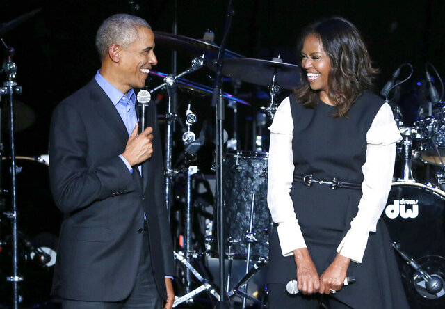 """FILE - Former President Barack Obama, left, and former first lady Michelle Obama appear on stage during a community concert at the Obama Foundation Summit on Nov. 1, 2017, in Chicago. The first guest of Michelle Obama's new podcast will have a familiar presidential face: Barack Obama. The former president will appear on """"The Michelle Obama Podcast"""" on Spotify, the Obama's Higher Ground and the streaming service announced Friday, July 24, 2020 . The podcast will debut on July 29. (AP Photo/Charles Rex Arbogast, file)"""