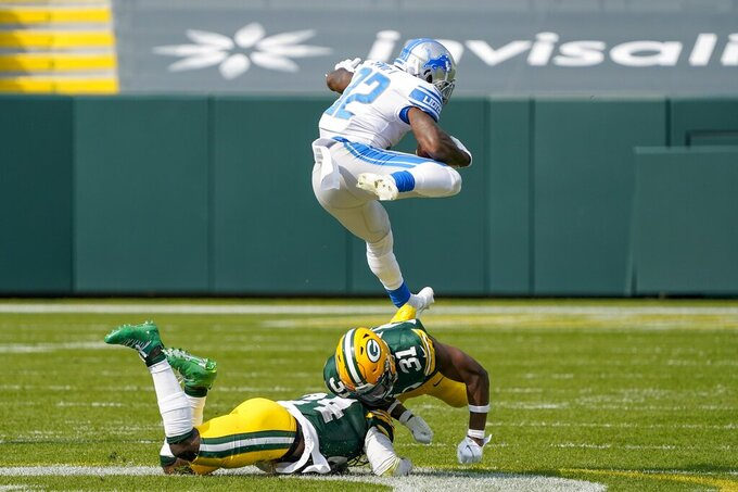 Detroit Lions' D'Andre Swift leaps over Green Bay Packers' Adrian Amos and Raven Greene during the second half of an NFL football game Sunday, Sept. 20, 2020, in Green Bay, Wis. (AP Photo/Morry Gash)