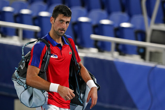 Novak Djokovic, of Serbia, walks off the court after losing a semifinal men's tennis match to Alexander Zverev, of Germany, at the 2020 Summer Olympics, Friday, July 30, 2021, in Tokyo, Japan. (AP Photo/Patrick Semansky)