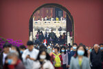 Visitors wearing face masks to protect against the coronavirus walk through in a doorway at the Temple of Heaven in Beijing, Thursday, Oct. 1, 2020. Millions of Chinese tourists usually would use their week-long National Day holidays to travel abroad. This year, travel restrictions due to the coronavirus pandemic mean that some 600 million tourists - about 40% of the population - will travel within China during the holiday that began Thursday, according to Ctrip, China's largest online travel agency. (AP Photo/Mark Schiefelbein)
