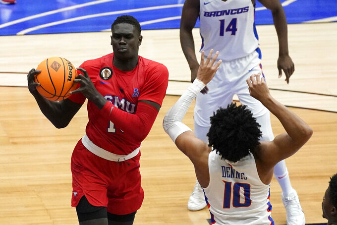 SMU forward Yor Anei grabs a rebound over Boise State guard RayJ Dennis, right, during the second half of an NCAA college basketball game in the first round of the NIT, Thursday, March 18, 2021, in Frisco, Texas. (AP Photo/Tony Gutierrez)