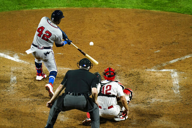 Atlanta Braves' Marcell Ozuna, left, drives in a run off Philadelphia Phillies pitcher Zack Wheeler during the sixth inning of a baseball game, Friday, Aug. 28, 2020, in Philadelphia. Ozuna was safe at first on a throwing error by shortstop Didi Gregorius. (AP Photo/Matt Slocum)