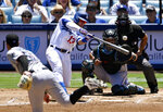Los Angeles Dodgers' Max Muncy, second from left, hits a solo home run as Miami Marlins starting pitcher Jordan Yamamoto watches along with catcher Jorge Alfaro, second from right, and home plate umpire Mark Wegner during the first inning of a baseball game Sunday, July 21, 2019, in Los Angeles. (AP Photo/Mark J. Terrill)
